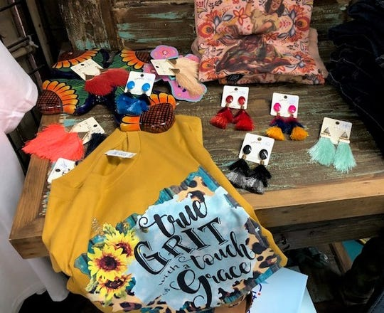 A small display at Gypsy Chix Boutique featuring earrings, a shirt and a sunflower cross.
