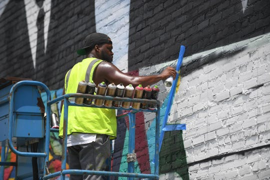 Paul Boyd III, works on a community-themed mural at the corner of East Church Street and Route 13 in Salisbury, Md. on Wednesday, July 11, 2019.