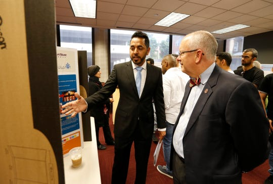 Missouri State University English Language Institute student Ali Alalqam presents his research project to MSU President Clif Smart during a reception at the Meyer Alumni Center on Thursday, July 11, 2019.