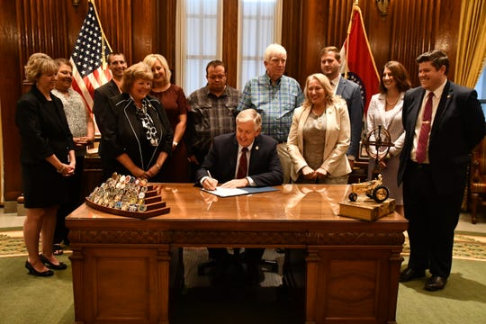 Missouri Gov. Mike Parson signs Hailey's Law at his office in Jefferson City, on Thursday. Hailey Owen's father, Markus Owens, center left, and Craig Wood's father, Jim Wood, center right, were on hand for the bill signing.