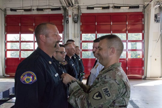 The Army Commendation Medal hangs on Spc. Bryan Garcia's uniform as the first responders are recognized for their live-saving efforts.