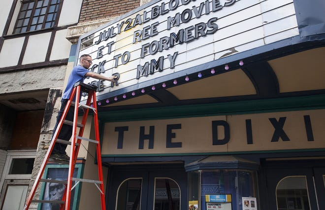 """Mike Collins,  who works at The Dixie theater, changes the marquee for their final week of screenings which will include the classic blockbusters """"Back to the Future,"""" """"Jaws,"""" E.T."""" and """"Raiders of the Lost Ark"""" in downtown Staunton on Wednesday, July 16, 2014."""