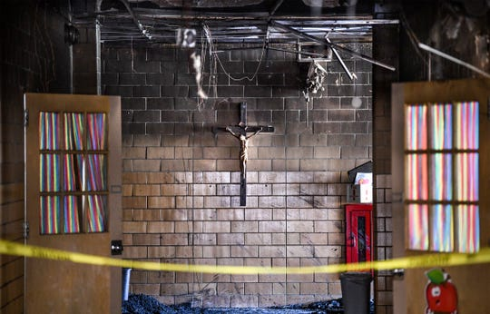 A crucifix remains in place, surrounded by soot and severe fire damage, at St. Elizabeth Ann Seton Catholic School Thursday, July 11, 2019, in St. Cloud. A fire was reported in the building just before 6 a.m. Thursday, July 4. Principal Kelly Vangsness said all of the fixtures in the entryway were melted or destroyed, but the crucifix remained on the wall in place.