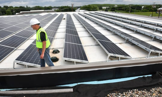 Facilities manager Kevin Korneck walks past rows of solar panels on the roof of the Stearns County Service Center construction project Wednesday, July 10, 2019, in Waite Park.