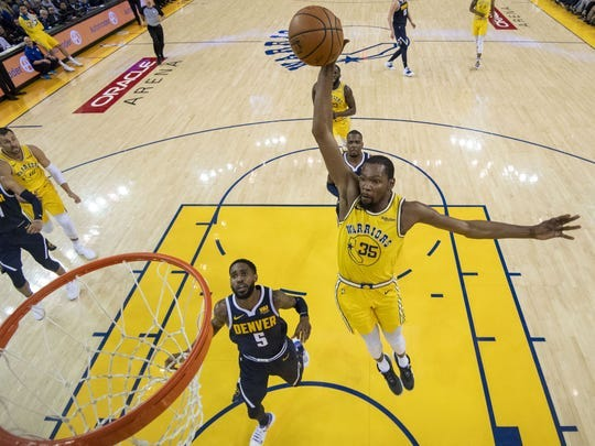 Golden State Warriors forward Kevin Durant (35) dunks the basketball against Denver Nuggets guard Will Barton (5) during the first half at Oracle Arena on April 2, 2019.