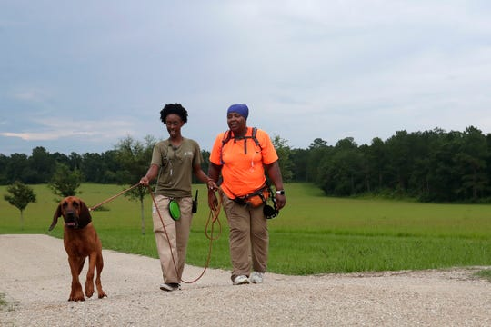 Tamar Smith, left, and Dr. Jolita Burns take EmmieRose for an evening stroll at Alford Greenway Tuesday, July 9, 2019.