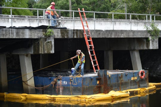 Sal Jimenez (top), of Concrete Cutting & Breaking Co., drills a hole in the concrete deck of the old bridge on Midway Road as part of its demolition on Wednesday, July 10, 2019, in Fort Pierce, as William Martinez, structural superintendent for Morrison-Cobalt, pulls in a containment boom to open the channel in the North Fork of the St. Lucie River. Work crews are removing the old 2-lane bridge as part of the $26.85 million widening of Midway Road before another new span can be built to allow for 4-lane traffic over the river.