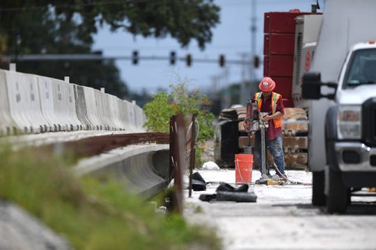 Sal Jimenez, of Concrete Cutting & Breaking Co., drills holes in the 18-inch thick concrete deck of the old bridge over the North Fork of the St. Lucie River on Midway Road, on Wednesday, July 10, 2019, in Fort Pierce. Work crews are removing the old 2-lane bridge as part of the $26.85 million widening of Midway Road before another span for the new bridge (left) can be built to allow for 4-lane traffic over the river.