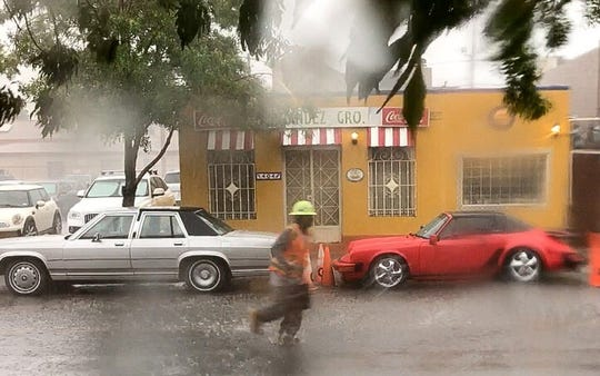 A worker runs through the rain Thursday in Downtown El Paso.