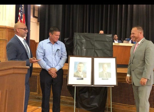 Vineland school board president Scott English (left) congratulates former BOE presidents, Jeff Bordley, (right) and Chris Jennings (middle) during an unveiling of their portraits. July 10, 2019