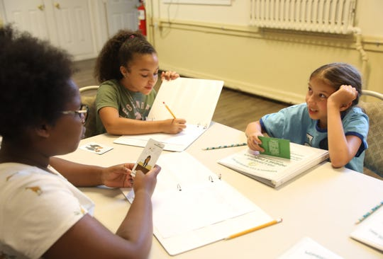 From left, Hannah Parker, 10, Nicole Peralta, 11, and Alexa Phipps, 10, play a game about money during Vivian London Crooks' 4-week financial literacy summer class at the Berea 7th Day Adventist Church in Nyack July 11, 2019.  London is an accountant with 20 years of experience holding a workshop to teach children about money.