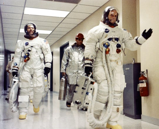 Apollo 11 commander Neil Armstrong waves to well-wishers in the hallway of the Manned Spacecraft Operations Building as he, Michael Collins and Buzz Aldrin prepare to be transported to Launch Complex for the first manned lunar landing mission.