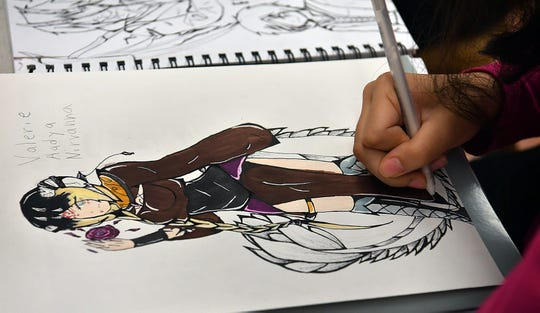 A students puts some finishing touches on her character during an Anime Art Camp class Thursday at the Kemp Center for the Arts.