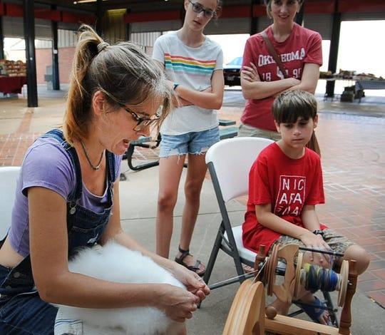 Tarah Niberg teaches a small crowd of people how to spin wool from an Angora rabbit during a class held Thursday morning at the Wichita Falls Downtown Farmer's Market.