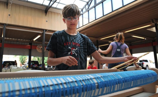 Kayden Lowder uses a rigid heddle loom to make a garment during a hands-on spinning and weaving class held at the Wichita Falls downtown Farmer's Market.