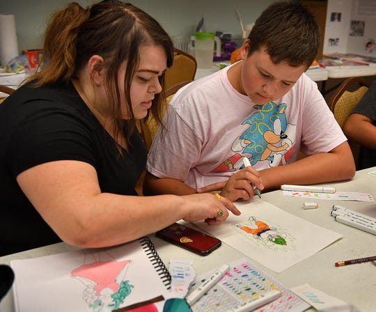 Art instructor Kelly Land gives Nick Wooten a few tips on shading while teaching her Anime Art Camp class at the Kemp Center for the Arts Thursday.