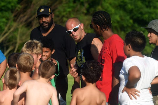 East Tigers varsity coach David Beaver, middle, talks to players during summer conditioning at their field at Armco Park. The Tigers have been around for more than six decades and serve players from all school districts.