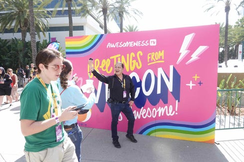 A YouTuber poses in front of a Greetings from VidCon sign at the ViCon convention in Anaheim