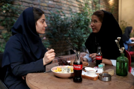 Two Iranians enjoy their time while two Coca-Cola stand on their table at a cafe in downtown Tehran, Iran, Wednesday, July 10, 2019.