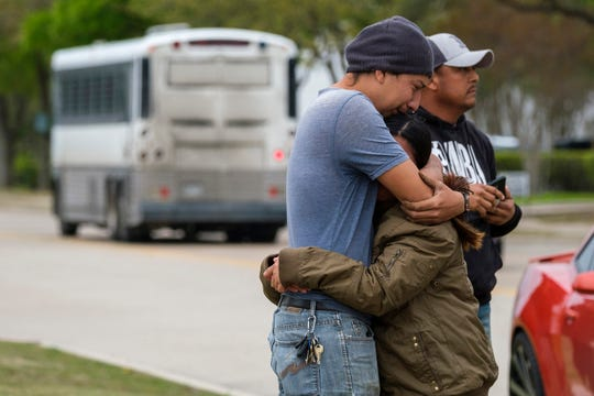 In this April 3, 2019, file photo, a couple who did not want to give their names embrace outside CVE Group as a bus from LaSalle Corrections Transport departs the facility in McAllen, Texas. Immigrant families and advocates are warning about planned arrests around the country by the Immigration and Customs Enforcement agency.