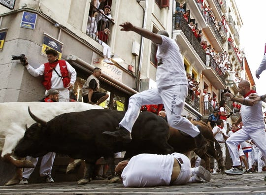 A runner jumps over a fellow reveler as they are chased during the running of the bulls Thursday in Pamplona Spain.  At least one runner was wounded by a bull.