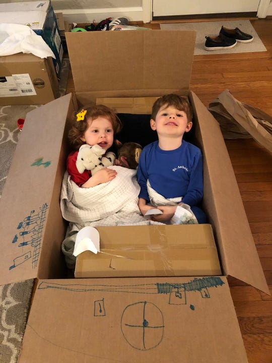 The Newman children sit in a box in their old Alexandria, Va., home.