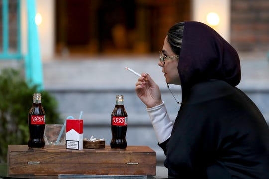 An Iranian smokes a Marlboro cigarette while two Coca-Cola stand on her table at a cafe in downtown Tehran, Iran, Wednesday, July 10, 2019.