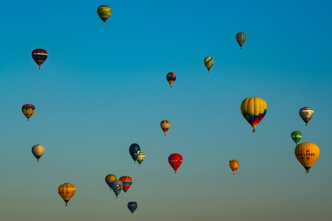 Hot air balloons fly over the city of Igualada.