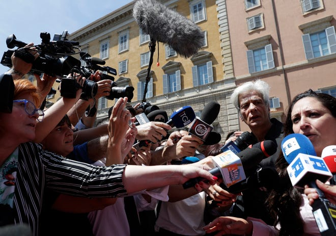 Pietro Orlandi, brother of Emanuela Orlandi who when missing in 1983, second from right, stands by his Laura Sgro as she speaks to the media after the Vatican reopened two tombs in the Teutonic Cemetery inside the Vatican, Thursday, July 11, 2019.