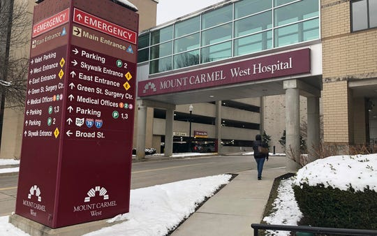 In this Jan. 15, 2019 file photo, the main entrance to Mount Carmel West Hospital is shown in Columbus, Ohio. The Mount Carmel Health System announced Thursday, July 11, 2019 that it's firing 23 more employees and changing leadership after investigating excessive painkiller doses given to dozens of patients who died.