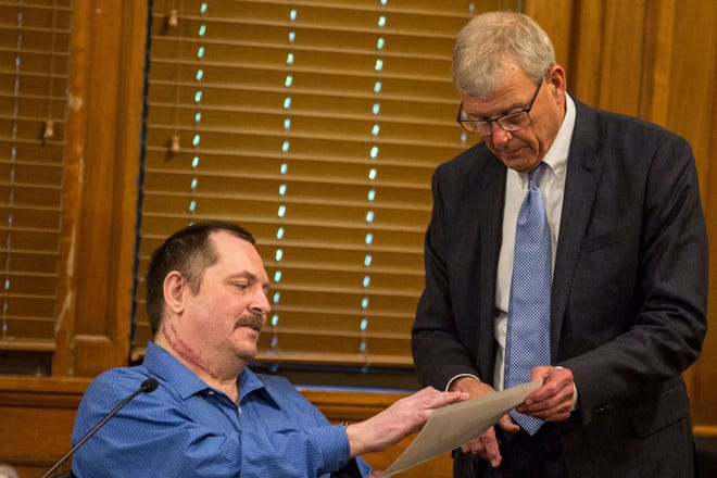 Aubrey Trail points to photos his attorney Joe Murray is holding while testifying during his murder trial at the Saline County Courthouse, Tuesday, July 9, 2019, in Wilber, Neb. Trail and girlfriend Bailey Boswell are charged with first-degree murder in the slaying of Sidney Loofe, whose body parts were found in ditches along a state highway, weeks after her November 2017 disappearance.