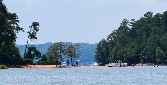 A pontoon is parked on part of a beach shore as people swim for recreation near Big Water Marina on Hartwell Lake Friday July 12, 2019. Nearby at the marina, the Lake Hartwell Poker run, July 11-13, benefits Meals on Wheels Anderson.