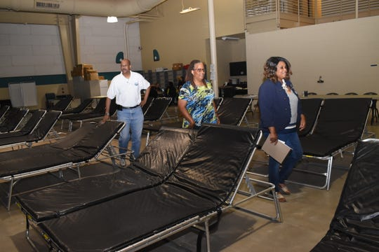 Felicia Calbert (far right), public affairs officer with the Department of Children and Family Services, gives La. State Rep. Ed Larvadain III for District 26 (far left) and his legislative aide LeCrete Robinson (center) a tour of the Mega Shelter's medical needs area Friday, July 12, 2019. The shelter has not officially opened.