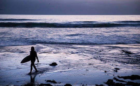 In this July 2, 2019, photo, a surfer walks out of the water after riding waves at dusk at Scripps Beach in San Diego. With hotel and airline loyalty programs, you can take the sting out of this year's travel costs by leveraging those expenditures to pay for next year's trip. (AP Photo/David Goldman, File)
