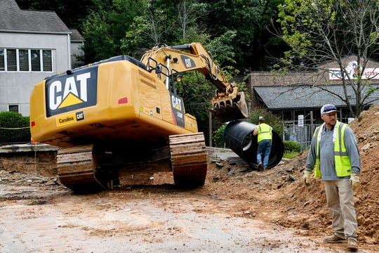A construction crew brought a new pipe to the scene of the sinkhole on Merrimon Avenue in North Asheville July 12, 2019.