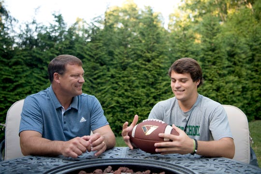 Former NFL quarterback Heath Shuler and his son, Christ School senior quarterback Navy Shuler, in the backyard of their home on July 2, 2019.