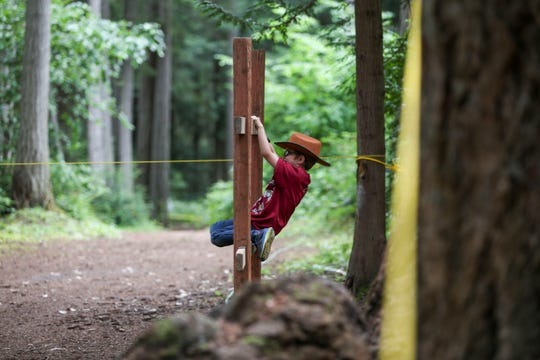 A Cub Scout climbs through the obstacle course during summer camp at the Kitsap County Fairgrounds.