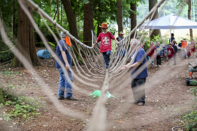 A Cub Scout walks across the rope bridge in the obstacle course at summer camp held this week at the Kitsap County Fairgrounds.