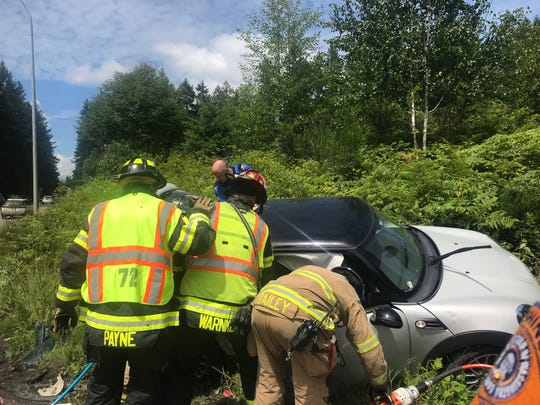 Emergency responders work at the scene of a crash on Highway 305 in Suquamish Friday afternoon.