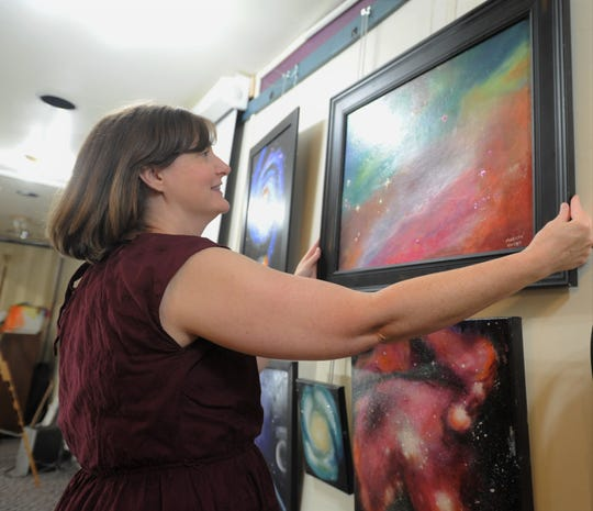Black Mountain-Tyson Library branch manager Melisa Pressley adjusts a painting that will be featured in a display in the education room at the library, which will celebrate the 50th anniversary of man landing on the moon.