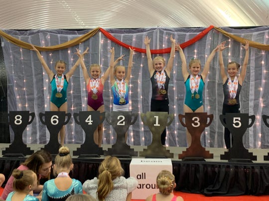Gracyn Areldge receiving her 4th Place All Around Medal.