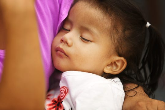 Gabi, 2, sleeps in her mother's arms at the Immigrant and Refugee Law Center at Roberts Paideia Academy in East Price Hill. Gabi has three older sisters and an older brother in Guatemala.