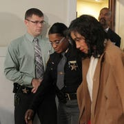 Tracie Hunter is escorted out of a Hamilton County courtroom on Dec. 5, 2014 after being sentenced to six months in jail. In the background at right is her attorney, Clyde Bennett II.