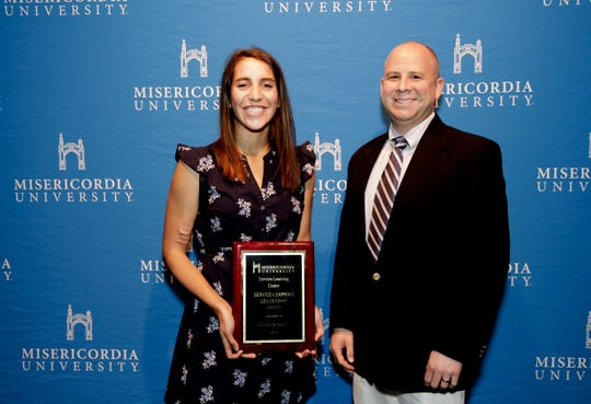 Misericordia University senior Julianna Norris of Edison, (left) was presented with the Service-Learning Leadership Award by Kevin Feifer, director of service-learning, at the annual Awards Ceremony on campus.