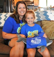 "Alicia Taylor and her daughter Laci, 6, with a stuffed dolphin she got at Clearwater Marine Aquarium in Florida, home of Winter from the movie ""Dolphin Tale."" Laci watches the movie or its sequel almost every day while doing breathing treatments for her cystic fibrosis."