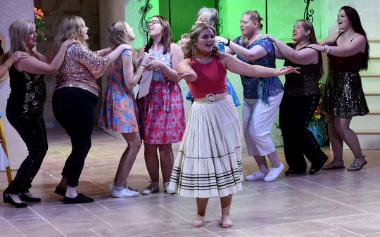 "Amanda Kittel and her choir of friends and bridesmaids sing ""Lay All Your Love on Me"" during a rehearsal for the Triple Locks Theatre's production of ""Mama Mia""."