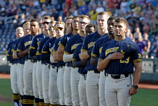 Erik Bakich and the Michigan players stand for the national anthem before Game 3 of the College World Series.