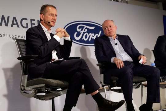 Volkswagen AG CEO Herbert Diess, left, and Ford Motor Co. CEO Jim Hackett  at  a news conference Friday in New York. The two automakers will to share electric vehicle platforms and self-driving software, potentially saving each company hundreds of millions of dollars.