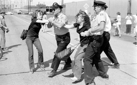 Police officers tussle with two women during an anti-busing demonstration in Pontiac, Michigan on September 1, 1971.