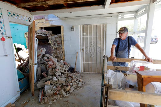 Eugene Johnson looks at the chimney collapsed by an earthquake at his home in Trona, Calif.